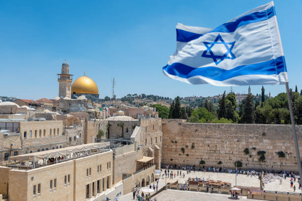 An Israeli flag blows in the wind from an elevated view of the Western Wall. Jewish orthodox believers read the Torah and pray facing the Western Wall, also known as Wailing Wall or Kotel in Old City in Jerusalem, Israel. It is small segment of the structure which originally composed the western retaining wall of the Second Jewish Temple atop the hill known as the Temple Mount to Jews and Christians.